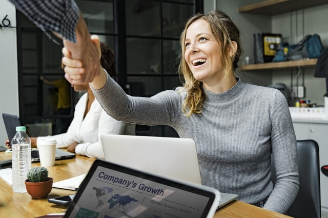 Picture of a lady at her desk with a laptop smiling happily as someone approaches to shake her hand. Show two people engaging in a happy friendly relationship.