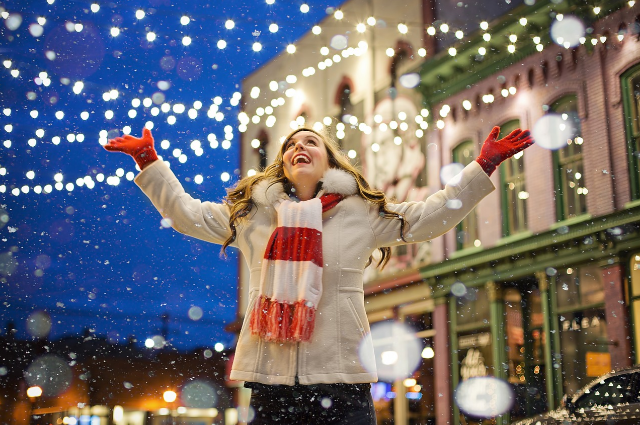 A picture of a lady starring in a christmas video outside in the street