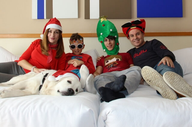 Image of a family sitting on a bed wearing silly christmas hats.