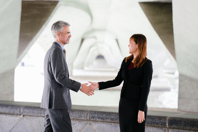 Photo of a man in a business suit and a lady in a business suite shaking hands in an office