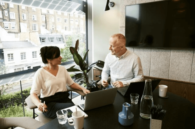 Image of two business people sharing workspace in a shared office
