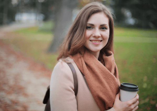Image of a woman holding a take away coffee cup outside in the autumn