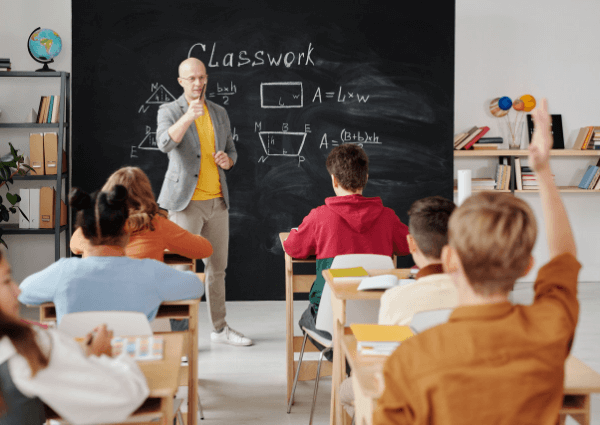Image of a teacher standing at a blackboard teaching school children