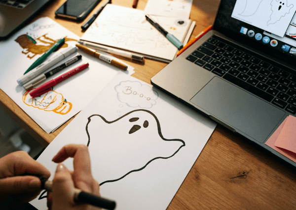 Image of a business man drawing a picture of a ghost for Halloween