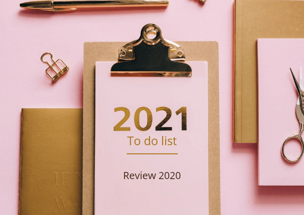An image of a clipboard and office stationery on a pink background. The clipboard reads 2021 to do list review 2020