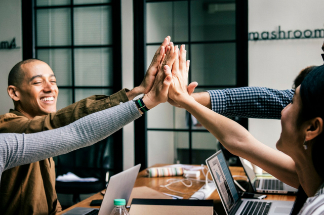 Picture of peoples hands high fiving each other in an office