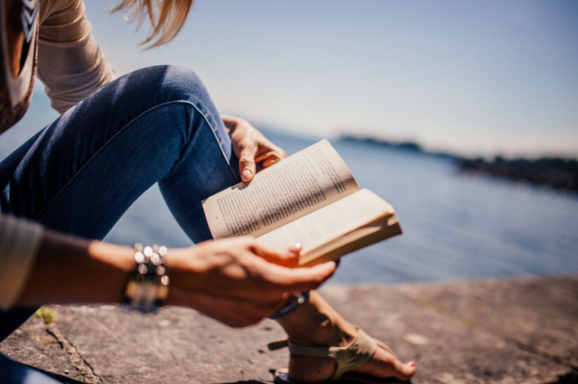 A picture of a lady reading a book in the sunshine by the water
