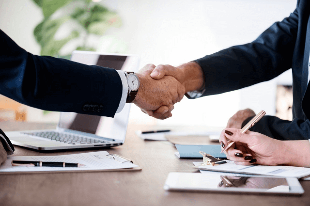 A picture showing two business people forming partnerships with a handshake