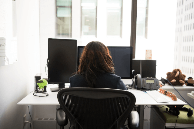 Picture of a female worker sitting at her desk starring at her computer looking bored