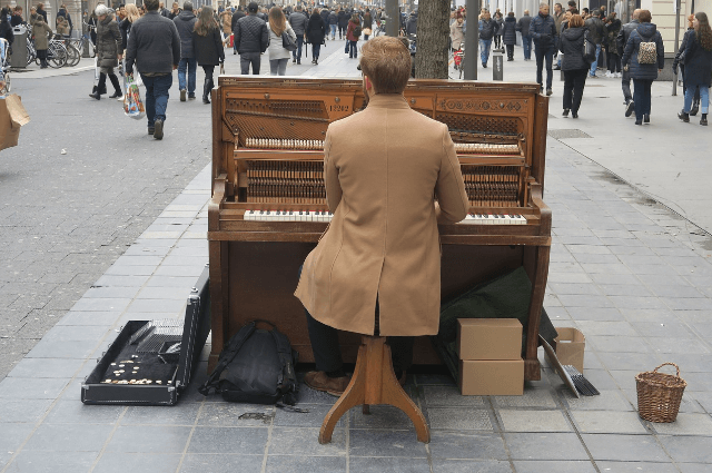 Picture of a man player a piano in the street amongst a busy crowded market