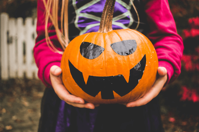 Picture of a girl dressed in as a witch holding a jack o lantern for Halloween
