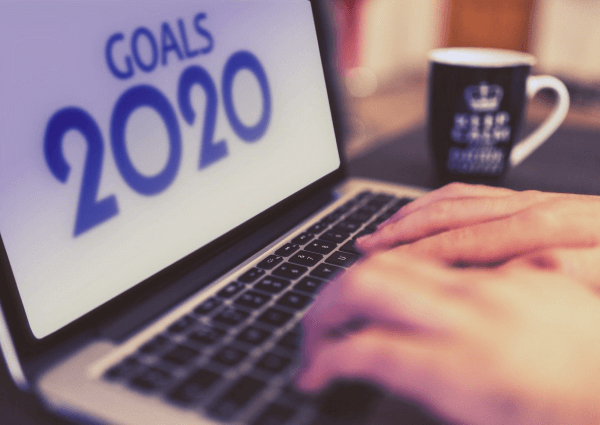 A picture of a man typing on a laptop with the words 2020 goals on the screen