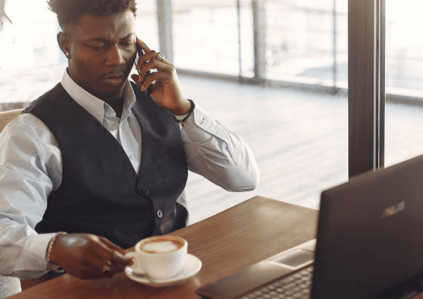 Picture of a man working from a serviced office with a laptop and a cup of tea whilst taking a call