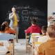 Image of a teacher standing at a blackboard teaching school children