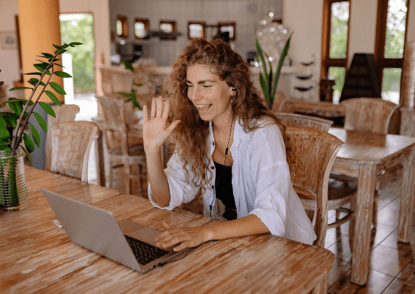 Picture of a woman smiling and waving on a networking video conferencing call