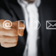 Image of a business man pointing at an email @ sign